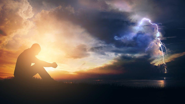 1 28 CH Man seated praying in sun rise while storm around Resurse